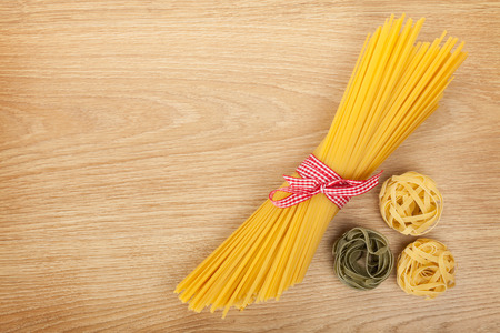 Bunch of spaghetti on wooden table background with copy space photo