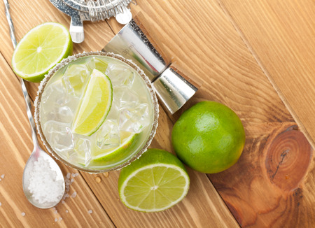 Classic margarita cocktail with salty rim on wooden table with limes and drink utensils Stock Photo