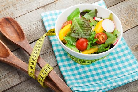Verse gezonde salade op houten tafel en keuken gebruiksvoorwerp