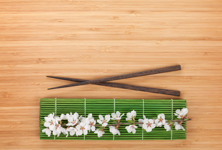 Chopsticks and sakura branch over bamboo mat on table with copy space photo
