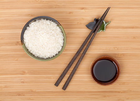 chop stick: Rice bowl, chopsticks and soy sauce over bamboo table Stock Photo