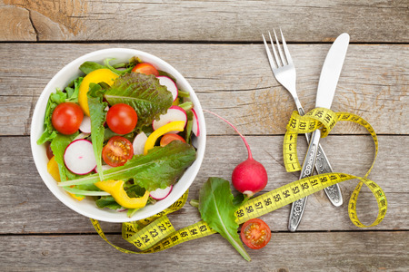 健康的なサラダと木製のテーブル上のテープを測定します。健康食品