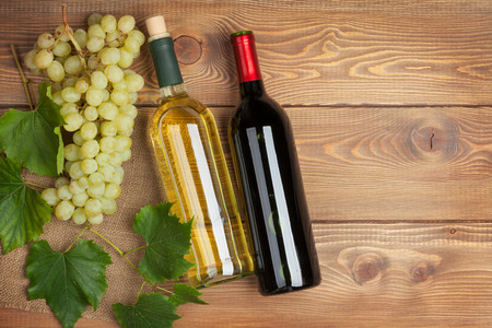 Red and white wine bottles and bunch of grapes on wooden table background with copy space photo