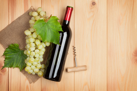 Red wine bottle and bunch of white grapes on wooden table background with copy space photo
