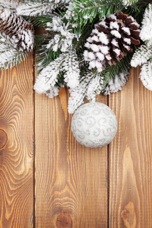 fir cones: Christmas fir tree with snow and bauble on rustic wooden board with copy space