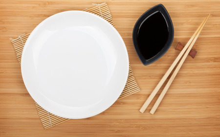 Empty plate, sushi chopsticks and soy sauce on bamboo table