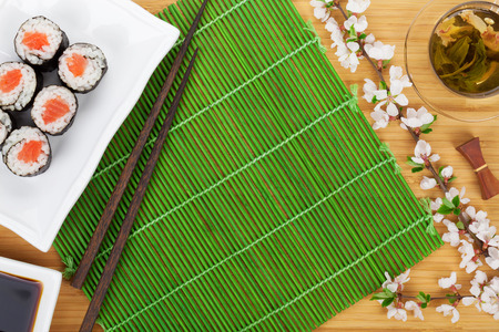 maki sushi: Sushi maki set, green tea and sakura branch over bamboo table with copy space Stock Photo