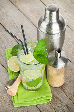 Fresh mojito cocktail and bar utensils. On wooden table photo