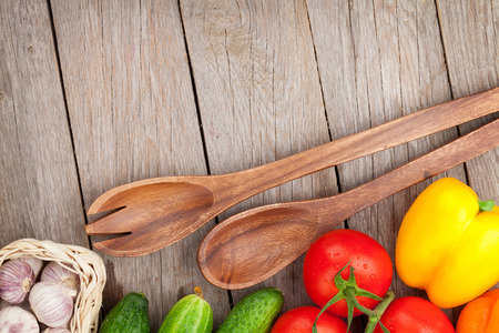 Fresh ripe vegetables and utensils on wooden table with copy space photo