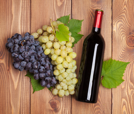 Red wine bottle and bunch of grapes on wooden table background photo