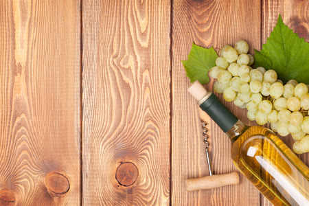 red and white wine: White wine bottle and bunch of white grapes on wooden table background with copy space