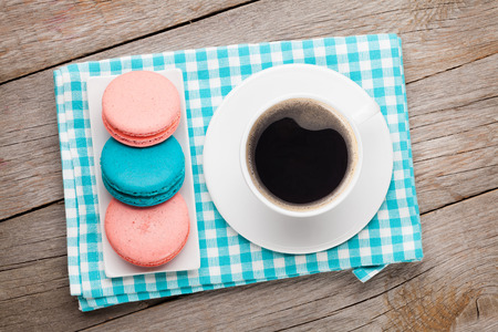 small cake: Colorful macaron cookies and cup of coffee on wooden table background