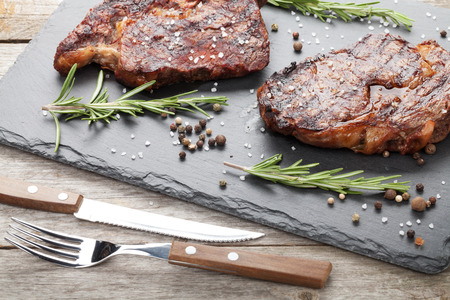 rib eye: Beef steaks with rosemary and spices on wooden table