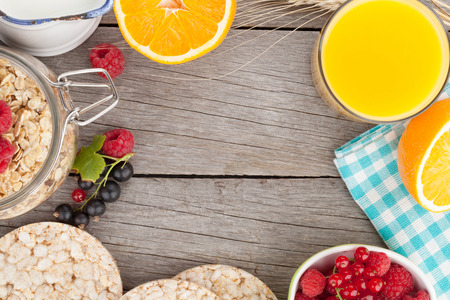 Healty breakfast with muesli, berries and orange juice. View from above on wooden table with copy space photo