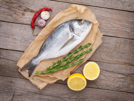 Fresh dorado fish cooking with spices and condiments on wooden table photo