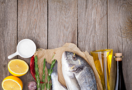 Fresh dorado fish cooking with spices and condiments on wooden table with copy space photo