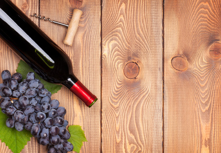 Red wine bottle and bunch of red grapes on wooden table background with copy space