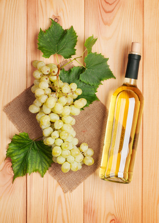 White wine bottle and bunch of white grapes on wooden table background photo