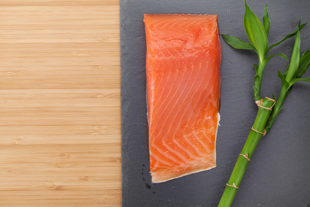 Fresh salmon fish on bamboo wooden table with copy space photo