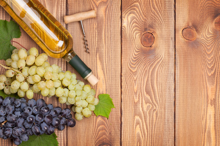 White wine bottle and bunch of grapes on wooden table background with copy space photo