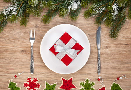 box tree: Gift box on plate, fir tree and christmas decor over wooden table background