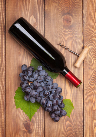 Red wine bottle and bunch of red grapes on wooden table background photo