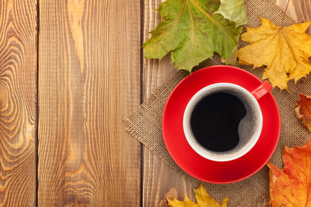Autumn leaves and coffee cup over wood background with copy space photo
