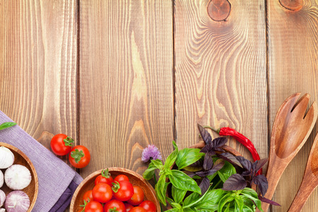green and purple vegetables: Fresh farmers tomatoes and basil on wood table. View from above with copy space Stock Photo