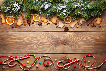 christmas spice: Christmas wooden background with snow fir tree, spices, gingerbread cookies and copy space