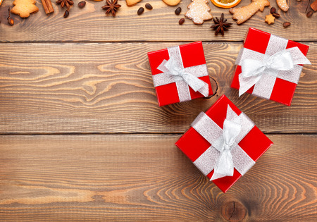 three gift boxes: Gift boxes over christmas wooden background with spices, gingerbread cookies and copy space