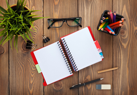 Office table with notepad, colorful pencils, supplies and flower. View from above with copy space photo