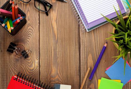 Kantoor tafel met kladblok, kleurrijke potloden, leveringen en bloem. Zicht van bovenaf met een kopie ruimte