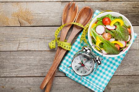 comida: Saludable ensalada fresca y cinta métrica en la mesa de madera. La comida sana