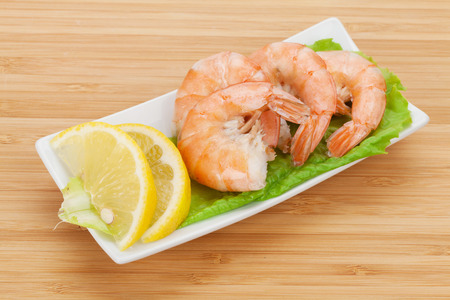 prepared shrimp: Cooked shrimps with lemon and salad leaves. View from above on wooden table