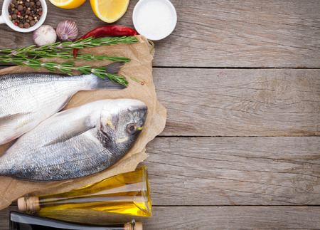 the dorada: Fresh dorado fish cooking with spices and condiments on wooden table with copy space Stock Photo