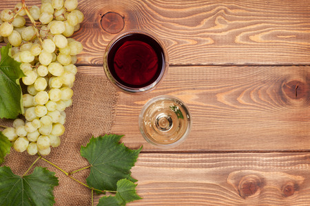 Red and white wine glasses and bunch of grapes on wooden table with copy space