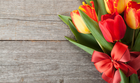 Fresh colorful tulips bouquet with ribbon and bow over wooden background with copy space photo