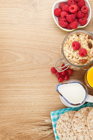 breakfast food: Healthy breakfast with muesli, berries and milk. On wooden table with copy space