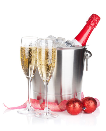 Champagne bottle in ice bucket, two glasses and christmas decor. photo