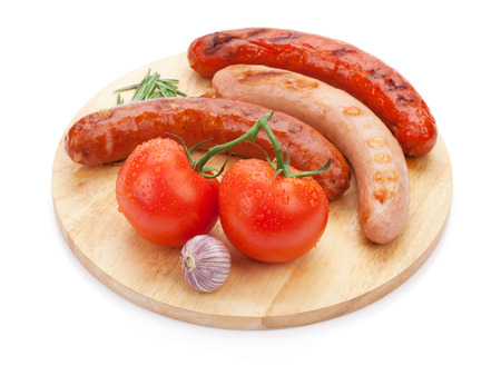 Various grilled sausages with condiments and tomatoes on cutting board. Isolated on white background photo