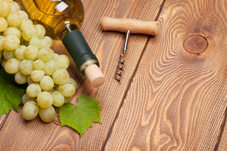 White wine bottle and bunch of white grapes on wooden table background with copy space photo