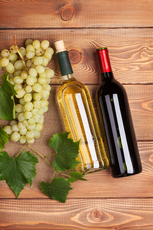 Red and white wine bottles and bunch of grapes on wooden table photo