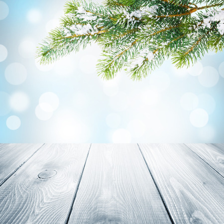 Christmas winter background with snow fir tree, wooden table and blurred bokeh photo