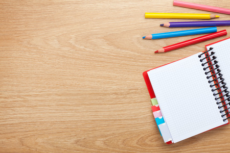 Office table with blank notepad and colorful pencils. View from above with copy space photo