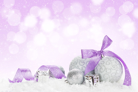 Christmas baubles and purple ribbon over snow bokeh background with copy space photo