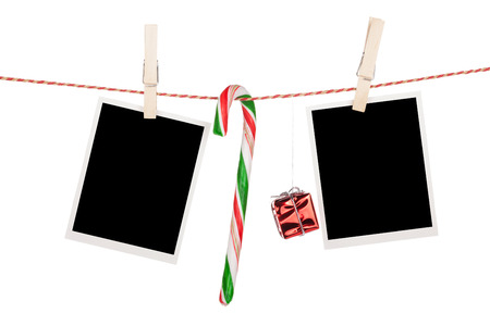 Blank photo frames and candy cane hanging on the clothesline. Isolated on white background photo