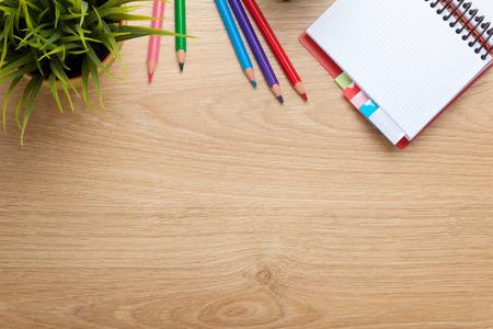 Kantoor tafel met bloem, lege blocnote en kleurrijke potloden. Zicht van bovenaf met een kopie ruimte