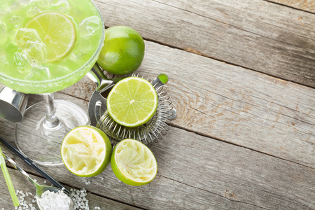 Classic margarita cocktail with salty rim on wooden table with limes and drink utensils Фото со стока