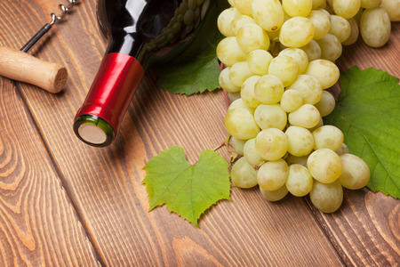 Red wine bottle and bunch of white grapes on wooden table background photo