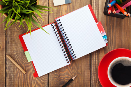 Office table with flower, blank notepad and coffee cup. View from above with copy space